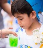 O rapaz pequeno graduou-se na água potável da escola do jardim de infância na escola Fotografia de Stock