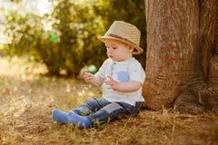 O rapaz pequeno grande-eyed pequeno em um chapéu senta-se perto da árvore no por do sol Foto de Stock Royalty Free