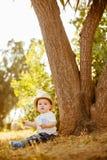 O rapaz pequeno grande-eyed pequeno em um chapéu senta-se perto da árvore no por do sol Fotografia de Stock
