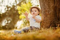 O rapaz pequeno grande-eyed pequeno em um chapéu senta-se perto da árvore no por do sol Fotografia de Stock Royalty Free
