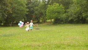 O rapaz pequeno guarda a menina pela mão e correm ao longo do gramado junto Movimento lento vídeos de arquivo