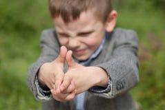 O rapaz pequeno imita uma arma Imagens de Stock