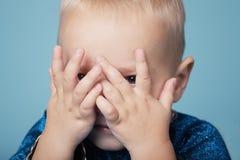 O rapaz pequeno joga o esconde-esconde Imagem de Stock