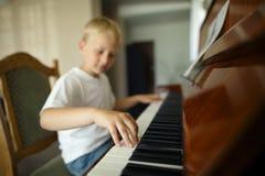 O rapaz pequeno joga o piano Foto de Stock