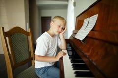 O rapaz pequeno joga o piano Imagens de Stock