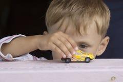 O rapaz pequeno joga um carro do brinquedo Fotos de Stock