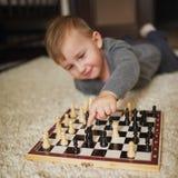 O rapaz pequeno joga a xadrez que encontra-se no assoalho foto de stock