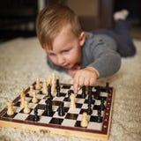 O rapaz pequeno joga a xadrez que encontra-se no assoalho imagens de stock royalty free