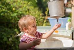 O rapaz pequeno lava suas mãos sob o distribuidor da água Imagem de Stock Royalty Free