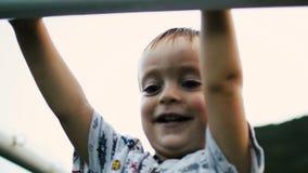 O rapaz pequeno levanta na barra vídeos de arquivo