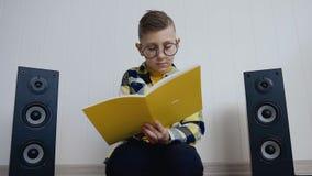 O rapaz pequeno louro nos vidros com livro de texto senta-se no assoalho em casa e grava-se algo lá em interessante em filme