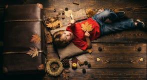 O rapaz pequeno louro que descansa com a folha no estômago encontra-se no assoalho de madeira nas folhas de outono O menino da cr imagem de stock royalty free