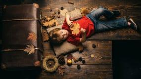 O rapaz pequeno louro que descansa com a folha no est?mago encontra-se no assoalho de madeira nas folhas de outono Os descontos o foto de stock royalty free