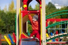 O rapaz pequeno louro senta-se em uma corrediça das crianças no campo de jogos Fotos de Stock Royalty Free