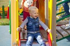 O rapaz pequeno louro senta-se em uma corrediça das crianças no campo de jogos Foto de Stock Royalty Free