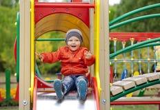 O rapaz pequeno louro senta-se em uma corrediça das crianças no campo de jogos Fotografia de Stock