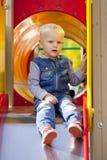 O rapaz pequeno louro senta-se em uma corrediça das crianças no campo de jogos Foto de Stock