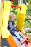 O rapaz pequeno louro senta-se em uma corrediça das crianças no campo de jogos Imagem de Stock Royalty Free