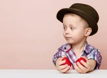 O rapaz pequeno minúsculo em um chapéu olha à esquerda nas mãos que guardam a Páscoa vermelha Fotos de Stock