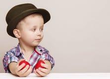 O rapaz pequeno minúsculo em um chapéu olha direito nas mãos que guardam o vermelho Foto de Stock