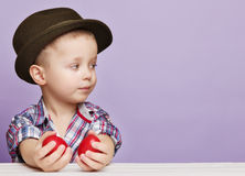 O rapaz pequeno minúsculo em um chapéu olha direito nas mãos que guardam o vermelho Fotos de Stock Royalty Free