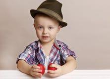 O rapaz pequeno minúsculo em um chapéu olha no visor nas mãos que guardam o Ea vermelho Imagem de Stock Royalty Free