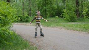 O rapaz pequeno monta em patins de rolo no parque vídeos de arquivo