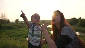 O rapaz pequeno mostra à mamã nos pássaros altos no ar livre do céu no movimento lento vídeos de arquivo