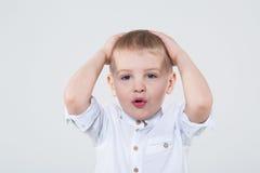 O rapaz pequeno na camisa branca agarrou sua cabeça imagem de stock