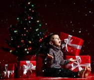 O rapaz pequeno na véspera do ano novo e do Natal está sentando-se sob a árvore fotografia de stock