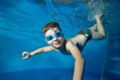 O rapaz pequeno nada debaixo d'água na associação, nas bolhas de sorriso, de sopro e em olhar-me A vista de debaixo da água Close Fotos de Stock Royalty Free