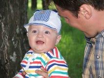O rapaz pequeno nas mãos do pai. Imagens de Stock Royalty Free