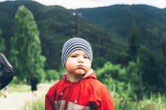 O rapaz pequeno nas montanhas faz as caras foto de stock royalty free