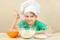 O rapaz pequeno no chapéu do cozinheiro chefe prepara a massa para o bolo de cozimento imagens de stock royalty free
