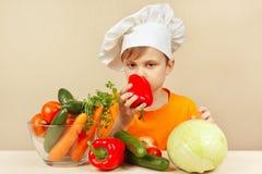 O rapaz pequeno no chapéu dos cozinheiros chefe escolhe legumes frescos para a salada na tabela Foto de Stock Royalty Free