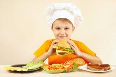 O rapaz pequeno no chapéu dos cozinheiros chefe aprecia cozinhar o Hamburger Fotos de Stock Royalty Free