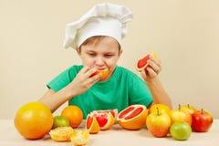 O rapaz pequeno no chapéu dos cozinheiros chefe come a toranja ácida fresca na tabela com frutos Fotografia de Stock