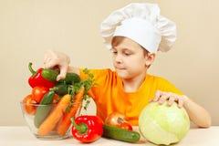 O rapaz pequeno no chapéu dos cozinheiros chefe escolhe vegetais para a salada na tabela Fotografia de Stock Royalty Free