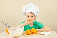 O rapaz pequeno no chapéu dos cozinheiros chefe está provando o bolo caseiro cozinhado Foto de Stock
