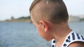 O rapaz pequeno no estrabismo da camisa das listras do marinheiro olha na distância no fundo do céu e do mar filme