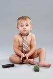 O rapaz pequeno no laço fala com o telefone de pilha Foto de Stock