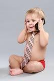 O rapaz pequeno no laço fala em um telefone de pilha Imagem de Stock