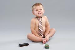 O rapaz pequeno no laço fala com o telefone de pilha Imagens de Stock