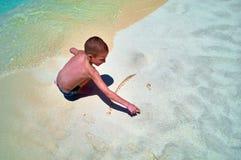 O rapaz pequeno no litoral pinta um sol de sorriso na areia A criança bonito pinta a cara do smiley na areia na linha da ressaca  Fotos de Stock Royalty Free