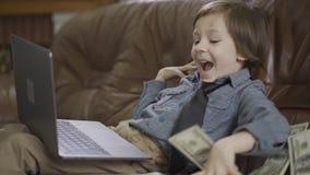 O rapaz pequeno no revestimento das calças de brim que senta-se no sofá de couro que joga no portátil Dólares que caem no sofá, a video estoque