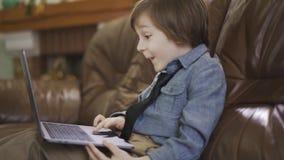 O rapaz pequeno no revestimento das calças de brim que senta-se no sofá de couro que joga no portátil, olhando na tela com surpre vídeos de arquivo