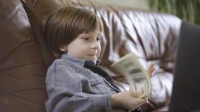 O rapaz pequeno no revestimento das calças de brim que senta-se no sofá de couro na frente do portátil que joga com o dinheiro Um vídeos de arquivo