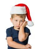O rapaz pequeno no tampão vermelho de Santa Claus fotografia de stock
