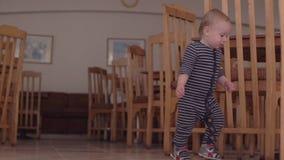 O rapaz pequeno nos macacões anda no bufete perto das cadeiras de madeira filme