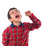 O rapaz pequeno nos vidros expressa sua alegria com seu punho fotografia de stock royalty free